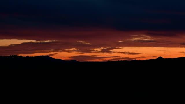 Orange cloudy dawn over silhouette of landscape
