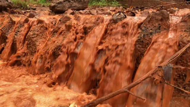 orange coloured stream polluted from the iron mine in itabirito brazil - iron ore stock videos & royalty-free footage
