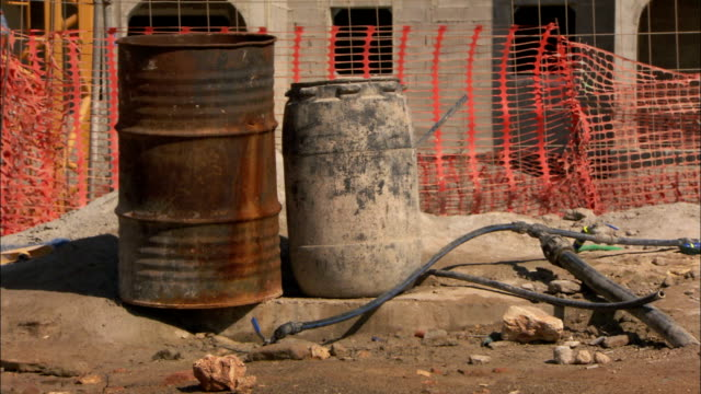 orange construction netting surrounds two barrels on a construction site. available in hd. - rusty stock videos & royalty-free footage