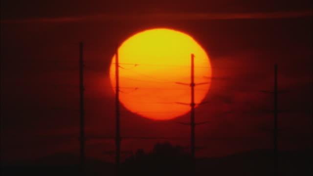 ws orange disk of sun slowly setting, silhouettes of high-tension electrical power transmission lines in foreground / wyoming, usa - electricity pylon stock videos & royalty-free footage