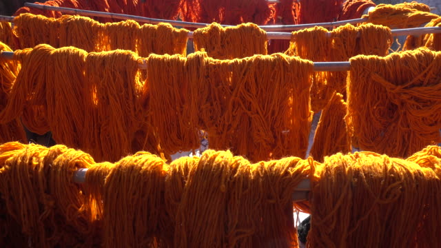 Orange dyed wool dries in the sun