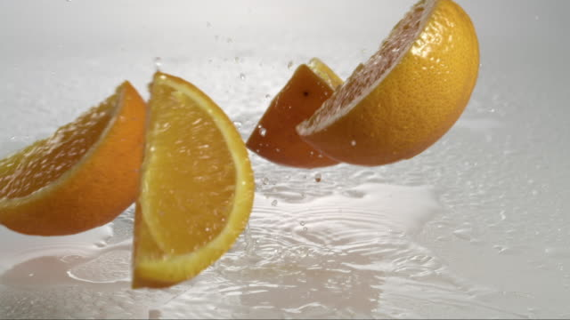 orange falling and creating splashing droplets - slice stock videos and b-roll footage