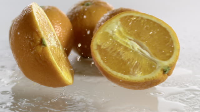 stockvideo's en b-roll-footage met orange falling and creating splashing droplets - vijf dingen