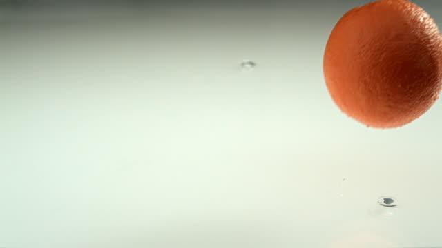 Orange falling into water