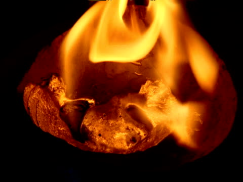 orange flames flicker over melting lead in preparation for fortune telling ritual - metallic look stock-videos und b-roll-filmmaterial