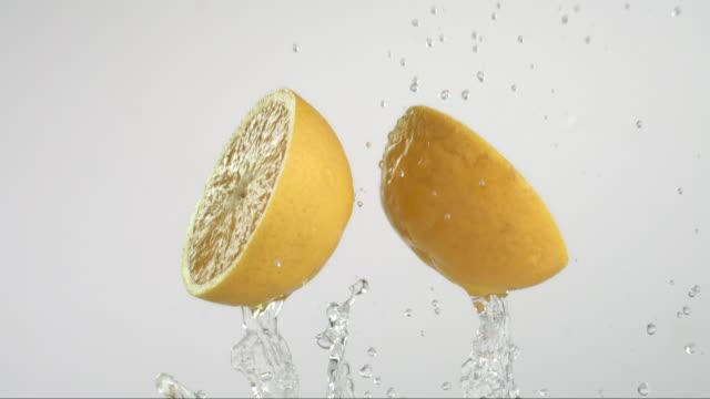 orange flying and creating splashing droplets - splashing droplet stock videos & royalty-free footage