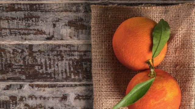 木材の背景にオレンジ色の果物。 - 荒い麻布点の映像素材/bロール