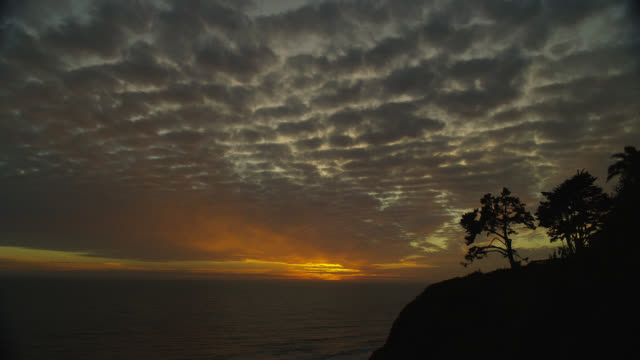 wide shot orange glow of sunset behind clouds over ocean with silhouetted cliff in foreground - 暮光 個影片檔及 b 捲影像