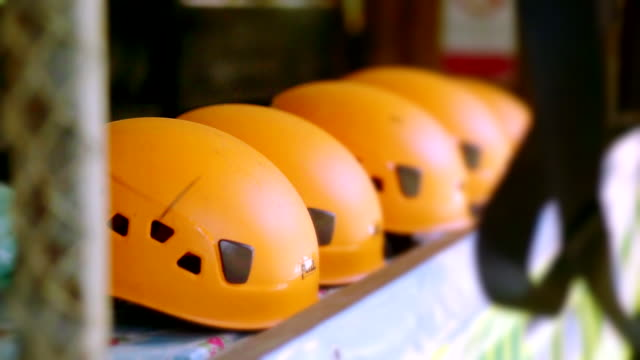 orange helmets zipline safety equipment in the adventure park. - imbracatura di sicurezza video stock e b–roll