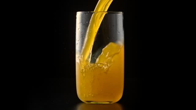vídeos de stock e filmes b-roll de orange juice drink pouring into glass - gaseificado