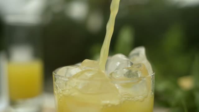 slo mo orange juice poured into glass, over ice, spain - orange juice stock videos & royalty-free footage