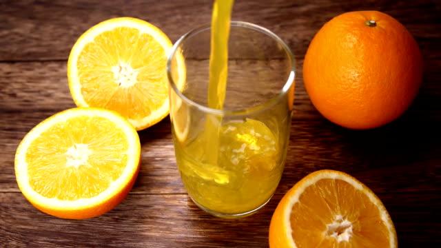 vídeos de stock e filmes b-roll de orange juice pouring into cup - sumo de laranja
