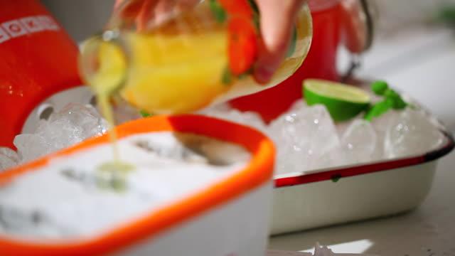 ecu r/f pan orange juice pouring into icecream tray for making icecream / seoul, south korea - オレンジジュース点の映像素材/bロール