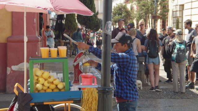 orange juice vendor at a street corner in san cristobal de las casas, chiapas, mexico - corner stock videos & royalty-free footage