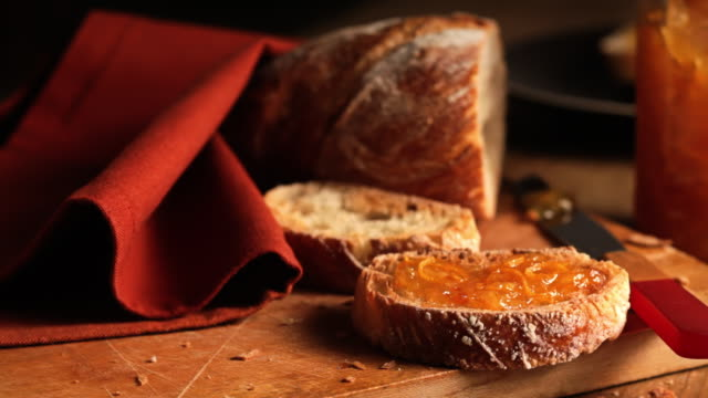 orange marmalade covers a slice of rustic bread. - bread stock videos & royalty-free footage