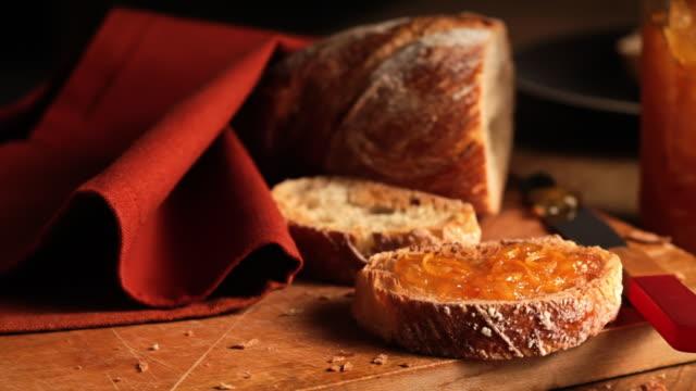vídeos de stock, filmes e b-roll de orange marmalade covers a slice of rustic bread. - geleia