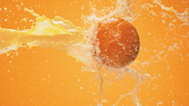 stockvideo's en b-roll-footage met slo mo orange juice plons in de lucht bijeen - sap