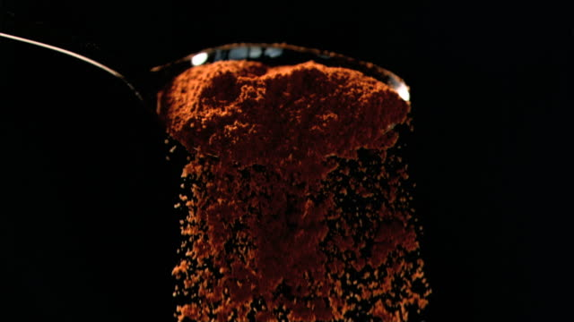 orange powder falling in super slow motion out of a spoon - 香辛料点の映像素材/bロール