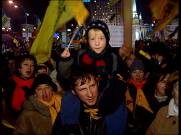 vídeos de stock, filmes e b-roll de general views of yushchenko supporters; crowds in square waving flags / child on father's shoulders / crowds - ucrânia
