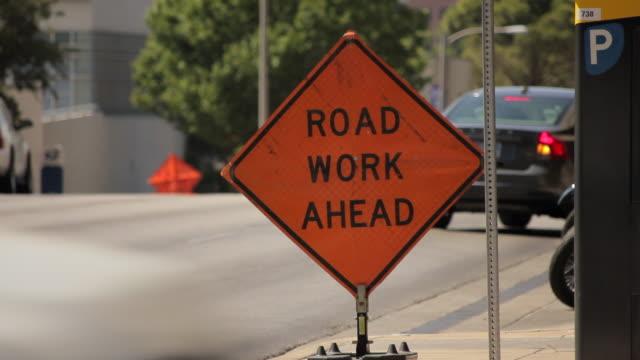 Orange road work ahead sign on street corner downtown