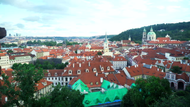 orange roof of old Prague city  among mountain range in evening