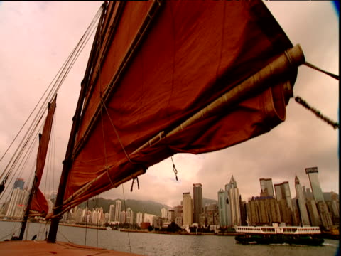 vidéos et rushes de orange sail of junk frames skyscrapers of hong kong behind - jonque