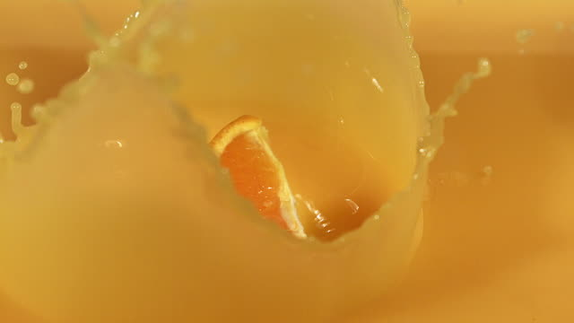 CU SLO MO Orange segment falling into orange juice / Vieux Pont, Normandy, France
