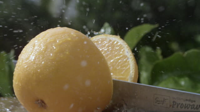 slo mo orange sliced in half on chopping board, spain - cutting stock videos & royalty-free footage