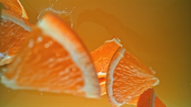 slo mo ld orange slices cut into smaller pieces falling into juice - medium group of objects stock videos & royalty-free footage