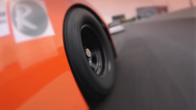 An orange stock car passes a white car on a racetrack.