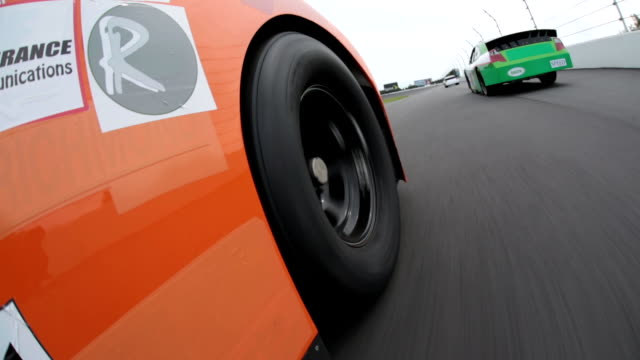 orange stock car passes white car in the curve to take the lead and speeds down race track straightaway. - car point of view stock videos & royalty-free footage