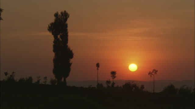 WS Orange sun setting in reddish sky / Volcanoes National Park, North Province, Rwanda
