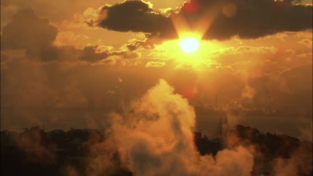 Orange sun shines as steam from hot springs rises into sky