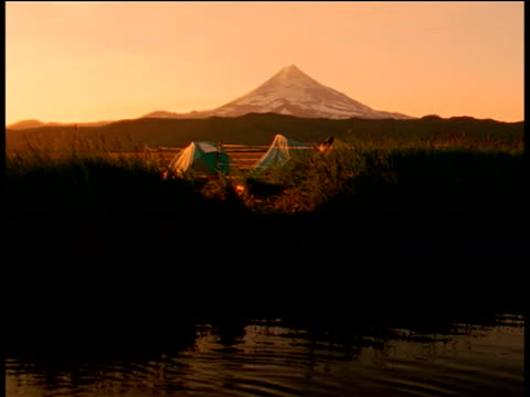 orange sunset glow on tents set up at rivers edge, mountain in background, unimak island, alaska - aleutian islands stock videos and b-roll footage
