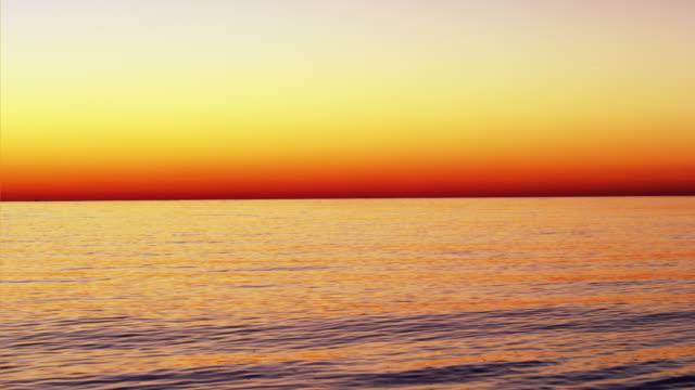 vidéos et rushes de orange sunset over ocean - orange