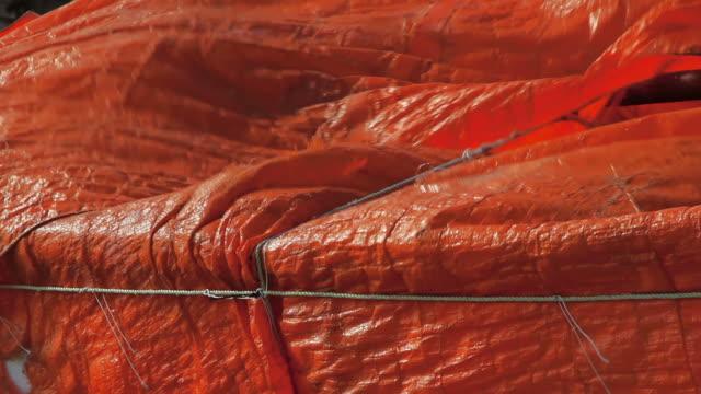 orange tarpaulin blowing in a gusty wind
