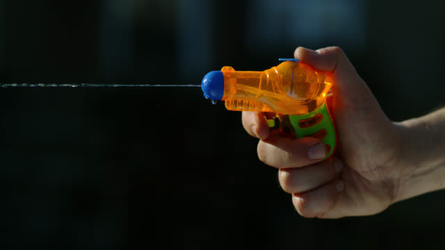slo mo orange toy water pistol squirting - 水遊び点の映像素材/bロール