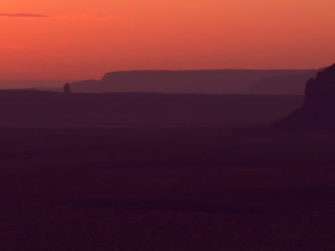 orange twilight and silhouetted mesas - artbeats stock videos & royalty-free footage