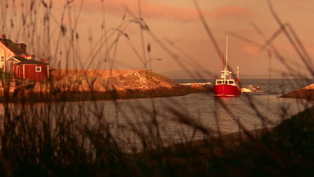 orange wide shot long shot fishing boat entering inlet from ocean / tall grasses in foreground / nova scotia, canada - inlet stock videos & royalty-free footage