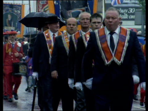 vidéos et rushes de orangemen march in rain down shankill road belfast 1990's - protestantisme