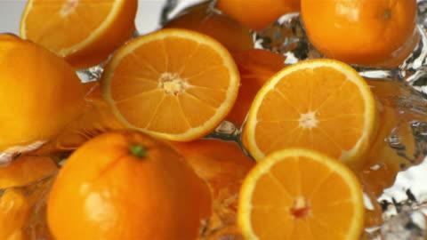 ecu slo mo oranges in water - orange stock videos & royalty-free footage