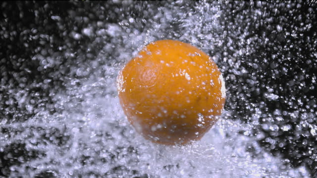 vídeos de stock e filmes b-roll de oranges splashing with water super slow motion 1000 fps - juicy