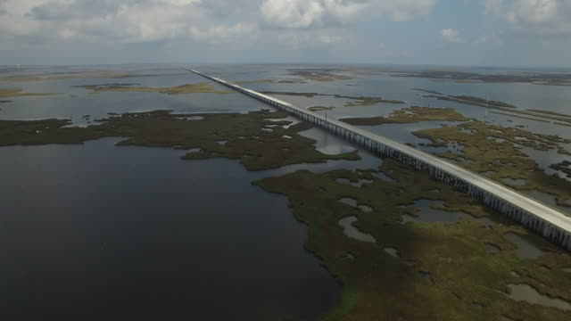 vidéos et rushes de orbit far from causeway - drone aerial 4k lake pontchartrain causewaygrand isle louisiana coast mississippi river bridge and barge everglades, gulf delta, with wildlife 4k transportation - gulf coast states