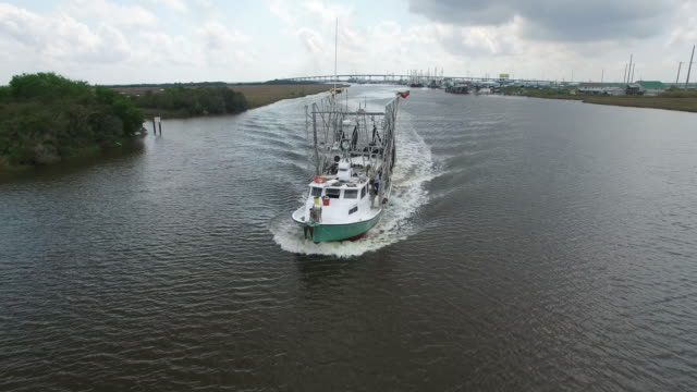 Orbit front to side of shrimp fishing boat - Drone Aerial View 4K Prawn fishing, shrimp boat, trawler, trawling for ocean fish in the open sea, heavy waves and nets in the water on Louisiana, mississippi coast, gulf coast 4K Transportation