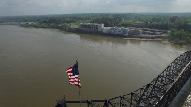 Orbit of american flag on top of bridge - Drone Aerial 4K Mississippi river bridge and barge 1of14, everglades, gulf delta, new orleans, st louis, with cruise boats sailing and wildlife 4K Transportation