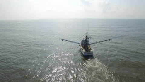 vídeos y material grabado en eventos de stock de orbit right to left behind shrimp fishing boat - drone aerial view 4k prawn fishing, shrimp boat, trawler, trawling for ocean fish in the open sea, heavy waves and nets in the water on louisiana, mississippi coast, gulf coast 4k transportation - barco pesquero