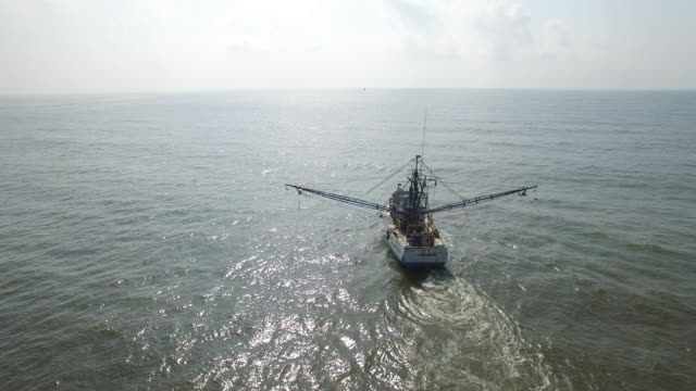 orbit right to left behind shrimp fishing boat - drone aerial view 4k prawn fishing, shrimp boat, trawler, trawling for ocean fish in the open sea, heavy waves and nets in the water on louisiana, mississippi coast, gulf coast 4k transportation - 水産業点の映像素材/bロール