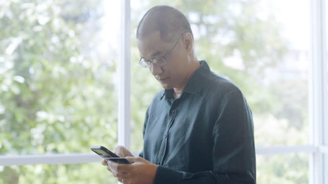 vídeos de stock e filmes b-roll de orbit shot of asian man making mobile payment on mobile phone. - one mature man only