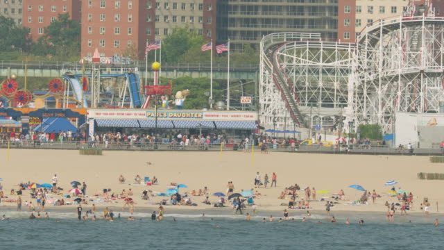 orbital shot of a crowd of people on the beach with the luna park in the background at coney island - sea bird stock videos and b-roll footage