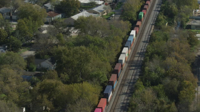 orbital shot of a freight train moving through west dallas suburb - 貨物列車点の映像素材/bロール